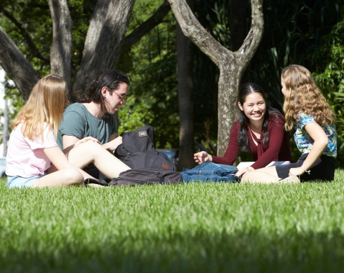 Four young people chatting in the park